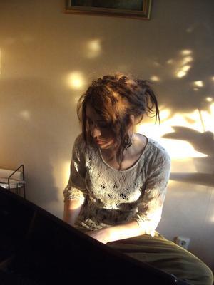 Vår dotter Heidi spelar piano mitt på julafton i dansande sol och skuggor,hemma hos oss i Bovallen.