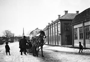 En av handlarna på Fiskartorget låter några barn följa med släden ner mot hamnen, förbi Hamngatans låga trähus som ger Västerås en prägel av småstad. Den lilla gatan som går in mot höger är föregångaren till Södra Esplanaden. Hörnhuset stod kvar ända till gatans breddning 1967. I det något mindre grannhuset mot norr, delvis skymt av hästen, låg en gång Hotell Västerås. Bortom det huset syns en ännu lägre byggnad där Västerås mejeri hade en mjölkbutik.