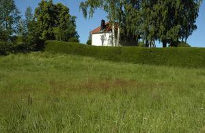 Oenighet. Här på åkern i sluttningen mellan Gustafs kyrkogård och stora vägen, finns det bygglov för garage och personalutrymmen. Men det är oenighet i den beslutande kyrkliga församlingen och när avgörande beslut skulle tas blev det återremiss.
