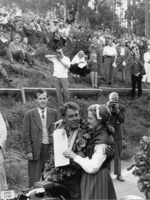 Ett foto från TT-loppet 1957 där kranskullan Barbro Bäcklund gratulerar segraren och legenden