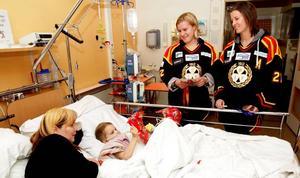 VÄLKOMMET AVBROTT. Femåriga Hanna Eriksson från Järbo kunde inte ta sig ut till lekrummet, men vill gärna ha besök på rummet. Brynäsdamerna Emma Eliasson och Joa Elfsberg kom med paket och visade upp sina OS-medaljer.