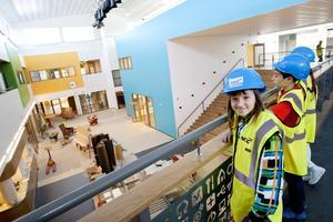 Eleverna Hanna Härkönen, William Maximurad och Sara Barmoro tittar stolt över sin nya skola.