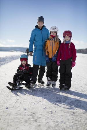Familjen Stenwall for fram över den blanka isen på skidskor. Det var Ingemar, mamma Maria, Cecilia och Linnea.