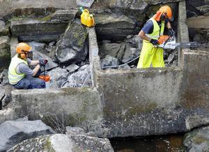 Personal från arbetsmarknadsenheten i färd med att förbättra fisketrappa i  Kramforsån.