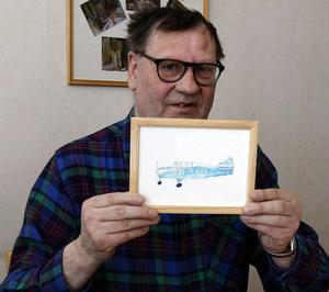 Kjell Sund visar upp en av sina teckningar där han målat ett flygplan.
