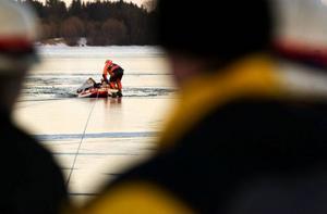 Räddningstjänsten drog upp isjakten ur vaken. Arbetet  försvårades av                       att isen var mycket tunn och inte gick att gå på. Isen brast så det bildades en öppen ränna i anslutning till vaken.  Foto: Håkan Luthman