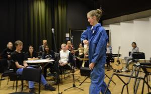 Dubbla roller. Louise Ehrson har snabbt bytt kostym för att inta sin andra roll i föreställningen. Bandet väntar på tecken att börja spela.
