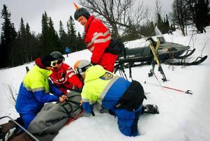 Janne Jonsson och Jörgen Nilsson från Röda korset hjälper en skadad 11-åring i slalombacken tillsammans med pistören Mikael Höglund och säkerhetschefen Rickard Svedjesten. Under påsken räknar man med 7–10 olyckor i backen varje dag.En flicka har ramlat i backen och skadat ena knät.