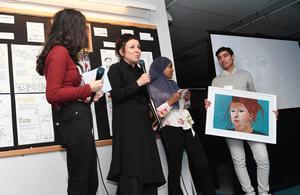 Olga Tokarczuk, Nobelpristagaren i litteratur 2018,  tar emot ett porträtt av sig själv målad av Anita Ali Asgar och Amran Adan Hersi, under sitt besök  på Rinkeby bibliotek. Foto Fredrik Sandberg / TT