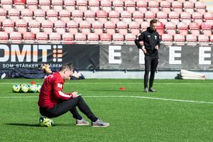 Försjunken på en boll. Axel drar upp de sista riktlinjerna samtidigt som spelarna värmer upp.  I bakgrunden assistenten Daniel Bäckström.