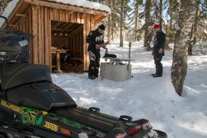 Mattias Eriksson hugger ved till korvgrillningen tillsammans med sonen Filip Nordberg. Vindskyddet i bakgrunden har Mattias byggt tillsammans med en vän.
