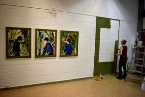 """Lotta Lindbeck från Rättviks kulturhus målar en """"ram"""" direkt på väggen."""
