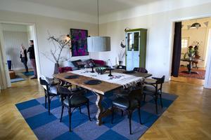 Den stora salen används som möteslokal. Här har de satt ihop två ärvda bord till en stor sittplats flankerade av restaurangstolar som de köpt på antik- och designbutiken Folks Interiör.