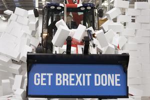 Storbritanniens premiärminister Boris Johnson sitter i en traktorhytt och bryter med skopa igenom en symbolisk mur med konservativa partiets slogan