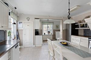 Det rymliga köket har ljus skåpinredning och plats för stort matbord och stolar. Foto: Diakrit/Privatmäklaren