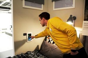 Jonas Fjäll, varuhuschef på Ikea Västerås, visar hur rummets belysning kan styras via en ipad på väggen.