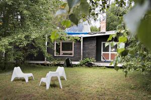 På södersidan av huset finns en gräsyta som familjen Nilsson använde som badmintonplan. Hans Johnell har placerat ut stolar vid husets alla sidor.