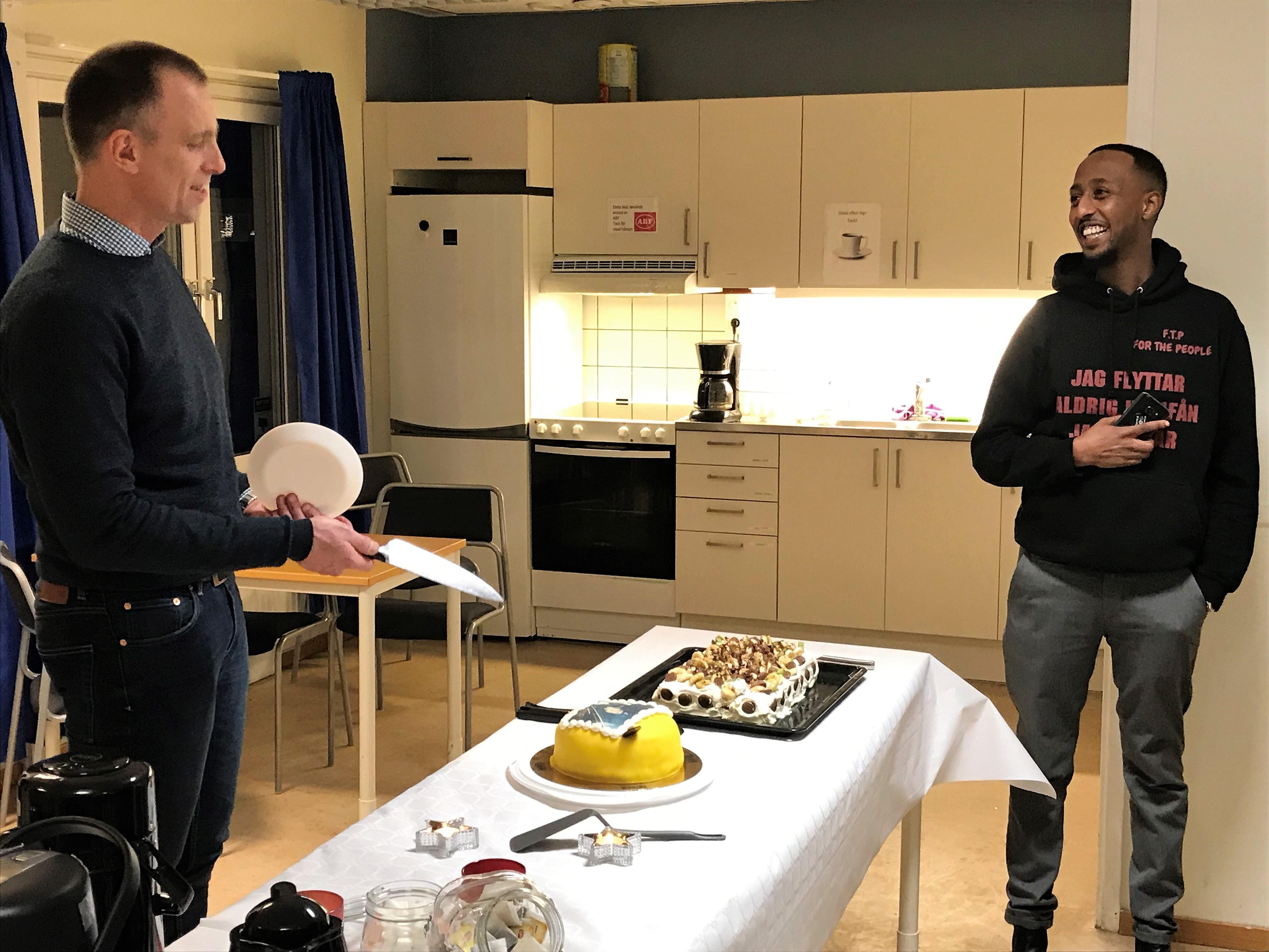 Fredrik Malm har plockat fram kniven för att hugga in på tårtan där han själv är avbildad. Till höger Khalid Mohammed, ordförande i For the people och Folkets hus i Vivalla.