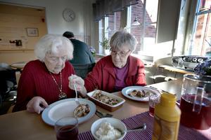 Två bord står i rummet och runt ett av dem sitter tre damer. Solen skiner dagen till ära in genom fönstret men även in i de äldres ögon. Caroline drar ner den persienn som stör mest. Sonja Klaesson får hjälp att lägga upp pannkakor på tallriken av Svea Embretsén.
