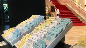 En gul, en vit och en blå ska ner i varsitt kuvert. Valsedlarna finns utanför röstningslokalen. En del plockar med sig en av varje in till valbåset. Andra tar precis de tre valsedlar de behöver.
