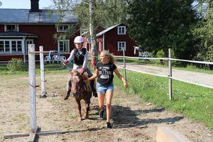 Lägerdeltagare Alice och hästen Lilla-My siktar in sig på en av ringarna. Här får hon lite hjälp av lägerledare Nova Fredin.