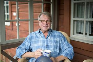 Göran Gudmundsson njuter av en kopp kaffe på den nybyggda verandan på sitt renoverade sommarställe.