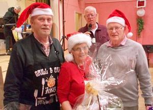 Ordförande Jan Holmgren, i bakgrunden, överräckte en delikatesskorg till medlemmarna i festkommittén, Lars-Göran Henriksson, Lena Hallkvist och Olle Paulsson. Foto: Roland Norrman