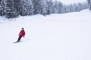 """Erik Norberg, 13 år, från Lit var först ner för Litsbacken. I snön har någon målat ordet """"ÄNTLIGEN"""" och en smileygubbe med rosa färg."""