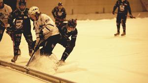 Snön yr runt skridskor, klubbor och boll när Rättviks Marcus Lindholm utmanas av Borlänges Oscar Jonsson.