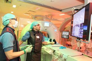Behandlingen på interventionsröntgenavdelningen utförs till stor del med ledning av bildskärmar. Här är det  röntgensköterskan Fredrik Ahlström och röntgenläkaren Tihomir Velinov som kollar att de är på rätt spår.