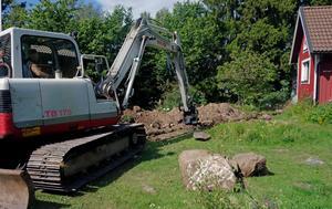 Grävmaskin gräver för kommunalt vatten och avlopp till ett fritidshus .
