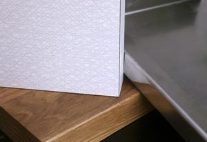 Olika material i bänkskivor. Ekträ, rostfritt stål och virrvarr.