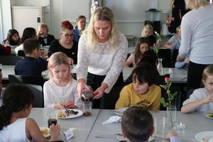Malin Samuelsson från Lindeskolans barn- och fritidsprogram häller upp kolsyrad dryck till Vita Hammarström Lindberg.