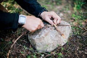 Att kunna göra sitt eget snöre är en bra kunskap i skogen. Här tillverkar Mikael ett bågdrillsnöre av en granrot.
