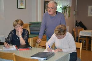 Tord Andersson har delat ut en uppgift till eleverna och kontrollerar hur  arbetet fortskrider för Solveig Hallberg Westlund och Gun Svensson.