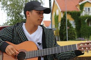 Matin stämmer gitarren innan han spelar upp en låt.
