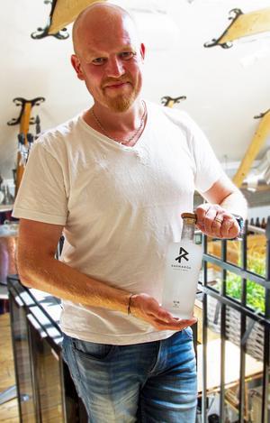 En stolt Jonas Larsson visar upp destilleriets prisvinnande gin Ragnarök, kryddad med bland annat lingon.