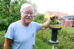 Torsten Johansson vid regnmätaren som har funnits i makarnas trädgård sedan de flyttade dit 1972. Mätaren har gått sönder och numer är det en behållare i plast som är mest tillförlitlig.