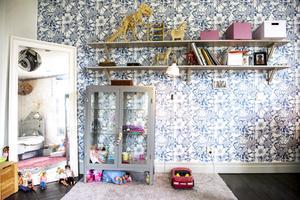 Den blåblommiga tapeten ger en lekfull känsla till dottern Klaras rum.