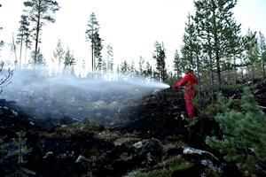 Robin Persson blöter den lilla glöd som finns kvar av branden.
