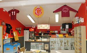 Tröjor i taket, klubbvimplar och pokaler i kafeterian i klubbhuset.