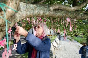 Lena Lundqvist hänger upp reflexer i ett träd i Henry Allards park i Örebro.