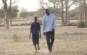 Skådespelaren Seydou Tall (Omar Sy) åker till Senegal för en bokmässa och träffar Yao (Lionel Louis Basse), ett ungt fan. Pressbild: Njuta films