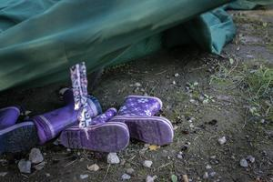 Under en tältduk i ett av de övergivna lägren ligger små barnstövlar kvar på marken.