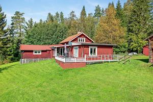 Timrat boningshus som byggts på i två omgångar. Dessutom finns ett härbre i två våningarpå tomten samt gäststuga och bastu. Foto: Patrik Persson.
