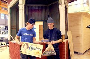 Joel Gustafsson och Jacob Lorenz har tillverkat luckor av trä. Här visar de gamla skyltar som hittades i kiosken.