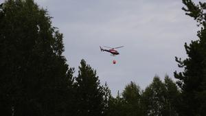 En helikopter som vattenbombar bränderna.