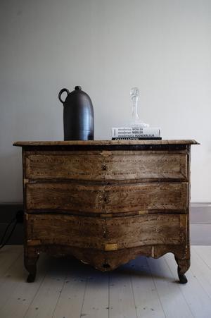 Byrån i vardagsrummet är ifrån sent 1700-tal. Molly föll direkt för dess skönhet och ömtålighet. De budade hem den på auktion ganska tidigt i sitt förhållande. Den gick över Mollys budgetgräns, men Sebastian höll upp lappen och till slut fick den följa med hem.
