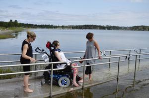 Malou Gustafssons personliga assistenter Ele Heinsaar och Zandra Risberg testar handikapprampen i Bergafjärden.