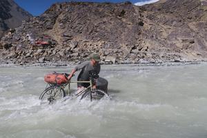 Det finns flera sidor av en cykelresa. Ibland trampar man på pedalerna och ibland drar man cykeln genom en flod till exempel.Här korsar Lars Bengtsson en flod i centrala Bartangdalen i Tadzjikistan år 2016